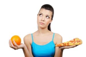 woman choosing between pizza and orange